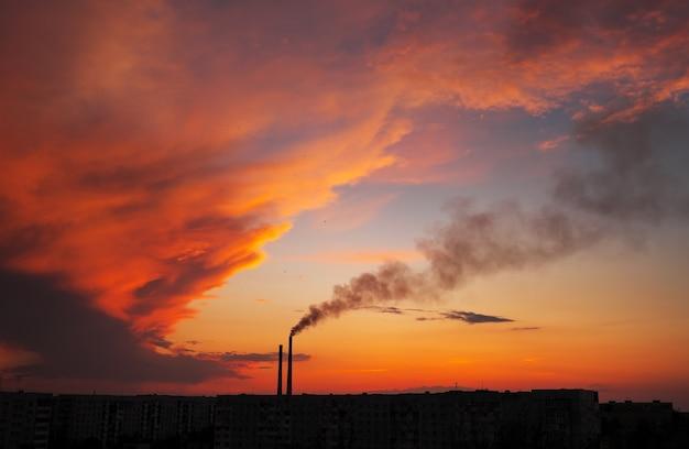 Pôr do sol mágico colorido. telhados de casas da cidade durante o nascer do sol. pássaros voando no céu. fumaça escura saindo da tubulação da usina termelétrica.