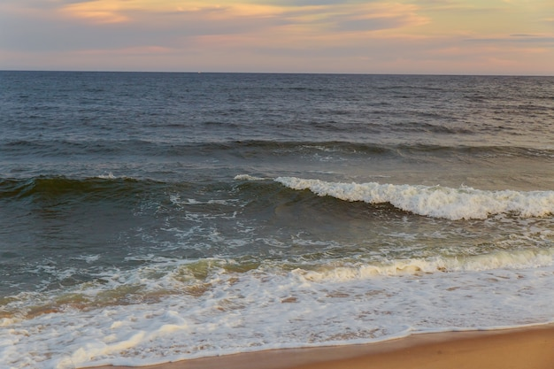 Pôr do sol mágico vista vista do mar com um lindo céu colorido, sol e nuvens. areia lisa na praia com espuma branca do oceano. karon beach phuket tailândia.