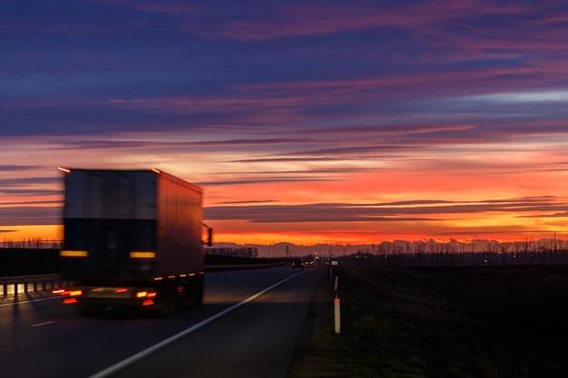 Pôr do sol muito colorido e um caminhão em movimento em uma estrada de asfalto