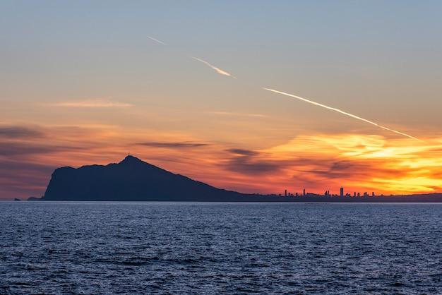Pôr do sol na cidade de benidorm, com um mar azulado.