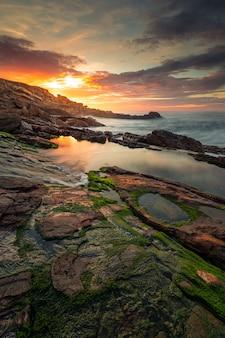 Pôr do sol na costa basca sob a montanha jaizkibel em hondarribia, país basco