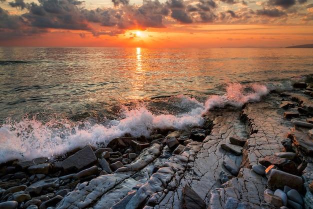 Pôr do sol na costa do mar negro, surf e rochas