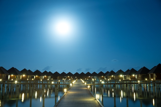 Pôr do sol na ilha das maldivas, resort de villas de luxo na água e cais de madeira.