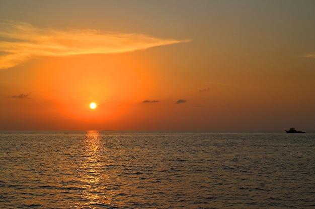 Por do sol na ilha de maldivas com barco e reflexão da luz solar no mar, vista do barco do curso. chave baixa.