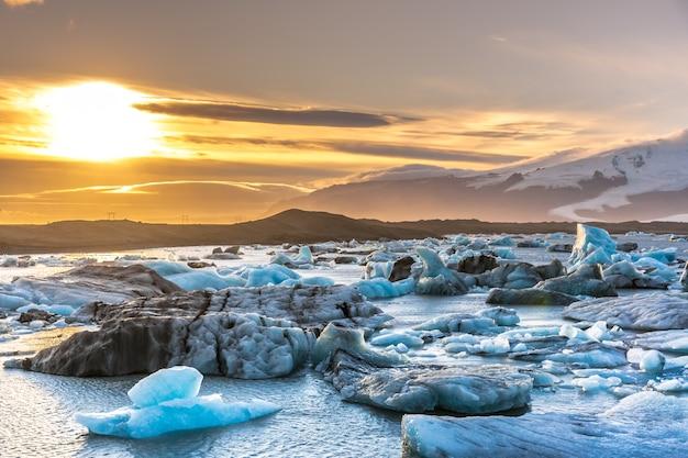 Pôr do sol na lagoa do iceberg na islândia, montanhas de capa de neve