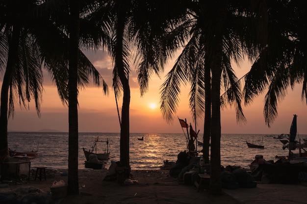 Pôr do sol na praia com coqueiros e barco de pesca