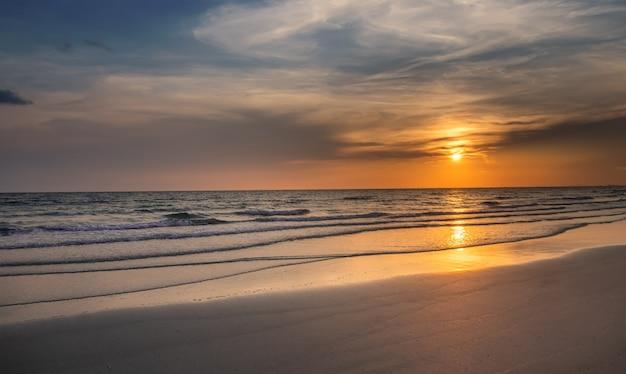 Pôr do sol na praia com o mar ondulado