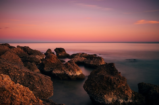 Pôr do sol na praia, com pedras em primeiro plano
