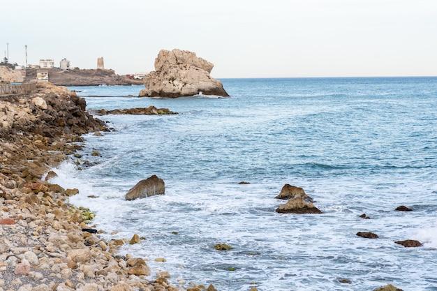 Por do sol na praia da rocha do corvo, málaga, espanha.