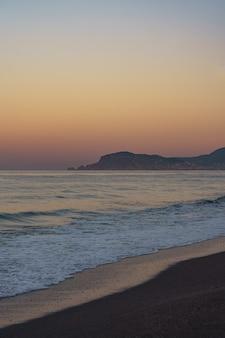 Pôr do sol na praia incrível com horizonte infinito e figuras de montanhas solitárias ao longe