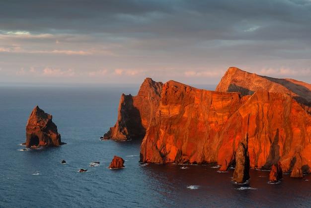 Pôr do sol nas falésias de san lorenzo, ao sul da ilha da madeira. últimos raios de sol iluminando as grandes rochas. portugal