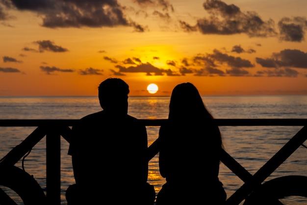 Pôr do sol nas maldivas, um casal na praia olhando à distância