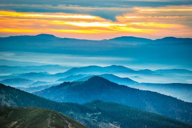 Pôr do sol nas montanhas. nuvens coloridas dramáticas sobre colinas azuis