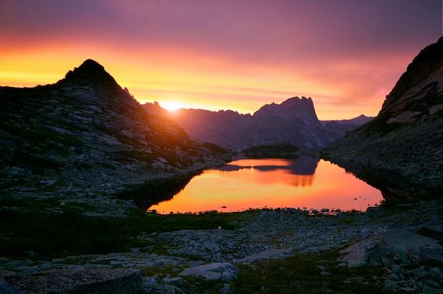 Pôr do sol nas montanhas perto do lago. luz do sol refletida no topo das montanhas