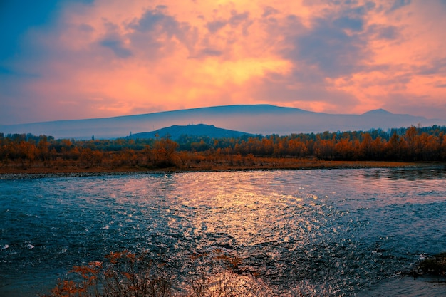 Pôr do sol nebuloso sobre o rio da montanha