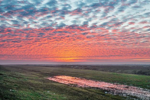 Pôr do sol no campo com lindas nuvens vermelhas e céu