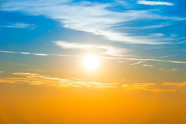 Pôr do sol no céu com nuvens laranja azuis e um grande sol