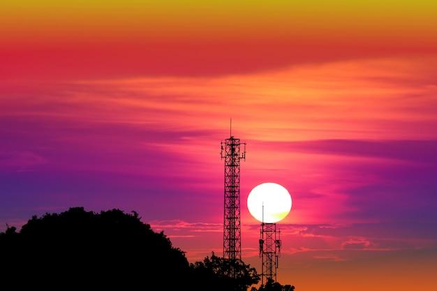 Por do sol no céu da noite e no polo de sinal coloridos da silhueta