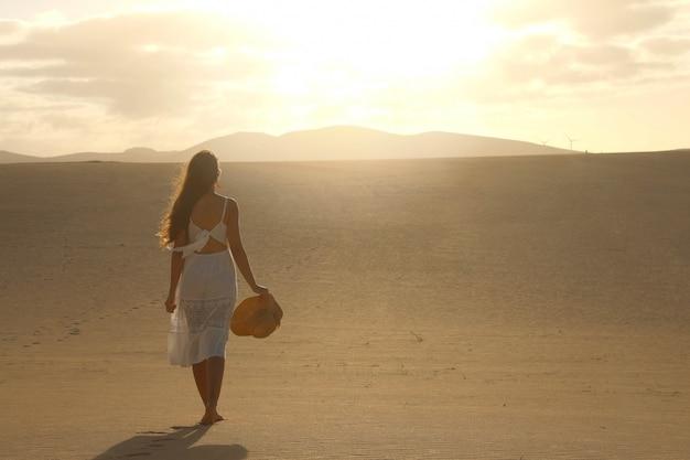 Pôr do sol no deserto. jovem mulher com um vestido branco, caminhando nas dunas do deserto com pegadas na areia durante o pôr do sol. menina andando na areia dourada em corralejo dunas, fuerteventura.
