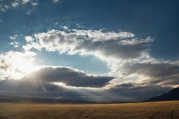 Pôr do sol no deserto, os raios do sol brilham através das nuvens. platô de ukok de altai. paisagens frias fabulosas. ninguém por perto