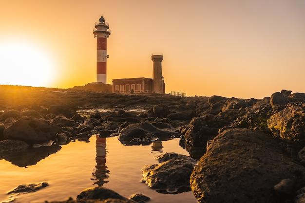 Pôr do sol no farol de toston perto do mar com o farol refletido, punta ballena perto da cidade de el cotillo, ilha de fuerteventura, ilhas canárias. espanha