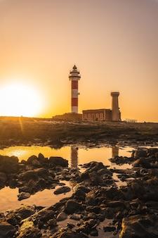 Pôr do sol no farol de toston perto do mar, punta ballena perto da cidade de el cotillo, ilha de fuerteventura, ilhas canárias. espanha