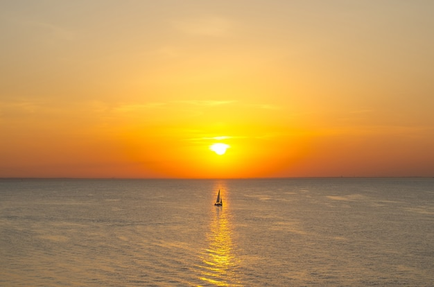 Pôr do sol no horizonte do mar do oceano, com um idiota de um veleiro na água refletida na luz.