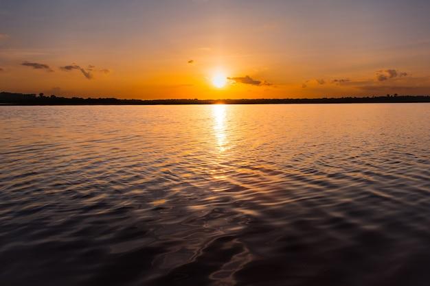 Pôr do sol no lago. belo pôr do sol por trás das nuvens acima sobre o backg de paisagem do lago