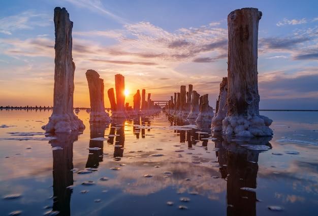 Pôr do sol no lago de sal. salmoura, sal e cavilhas de madeira. extração de sal.