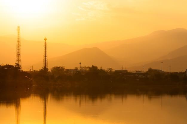 Pôr do sol no lago enevoado com linhas de eletricidade no fundo