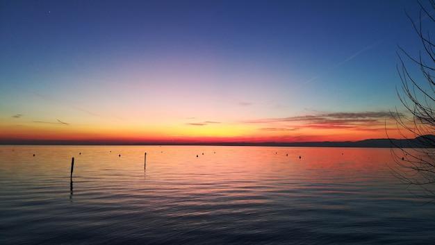 Pôr do sol no lago garda, itália. paisagem italiana. pier em perspectiva