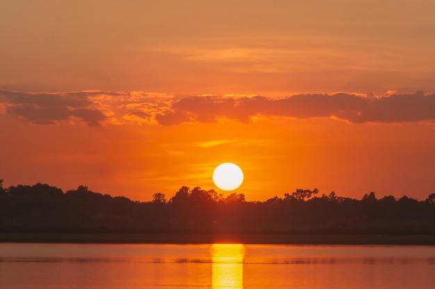 Pôr do sol no lago. por do sol bonito atrás das nuvens acima do fundo excedente da paisagem do lago. céu dramático com nuvem ao pôr do sol