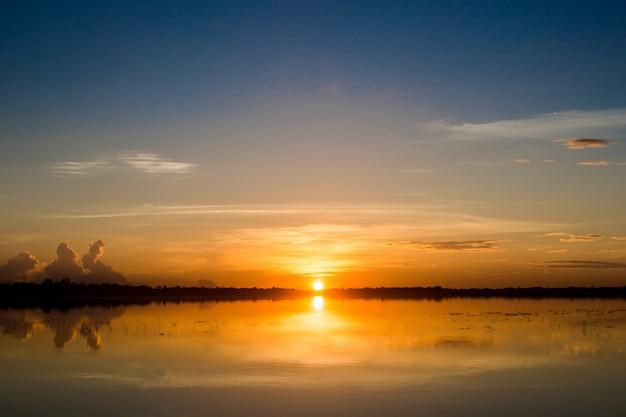Pôr do sol no lago. por do sol bonito atrás das nuvens acima do fundo excedente da paisagem do lago.