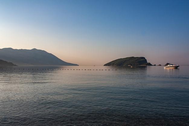 Pôr do sol no mar adriático de montenegro na cidade de budva com o barco e a rocha no mar