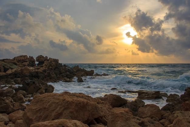 Pôr do sol no mar com pedras.