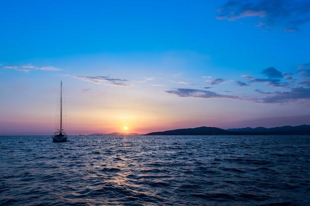 Pôr do sol no mar com um veleiro no horizonte. horizonte do mar.