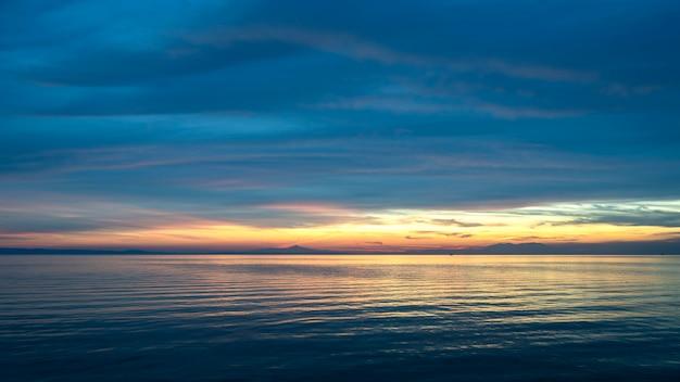 Pôr do sol no mar egeu com terra à distância, água e raios de sol, grécia