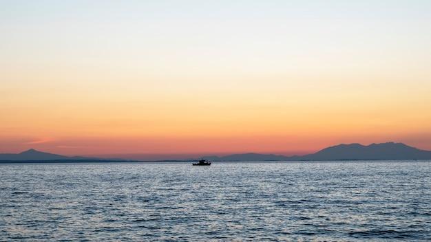 Pôr do sol no mar egeu, navio e terra ao longe, água, grécia