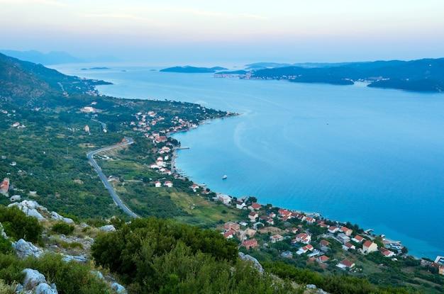 Pôr do sol no mar, ilhas croatas e a vila de viganj na costa (península de peljeã… â¡ac, croácia) e a vila e ilha de korcula ao longe