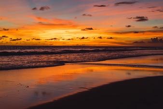 Pôr do sol no oceano. lindo céu brilhante, reflexo na água, ondas.