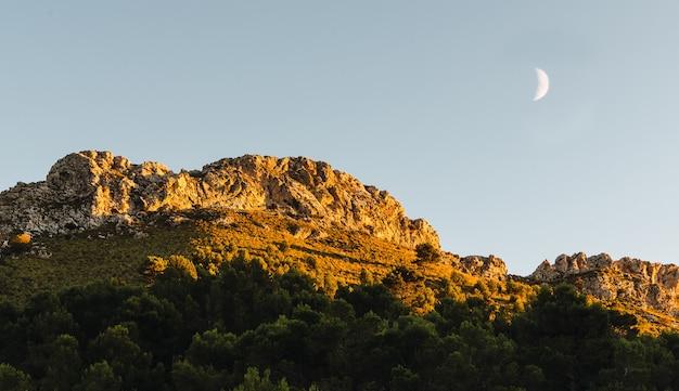 Pôr do sol no pico da montanha com a lua minguante.