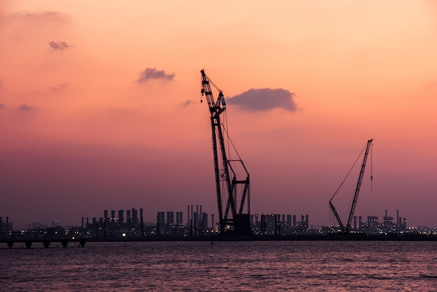 Pôr do sol no porto de dubai, emirados árabes unidos. silhueta de guindastes em um fundo de céu brilhante
