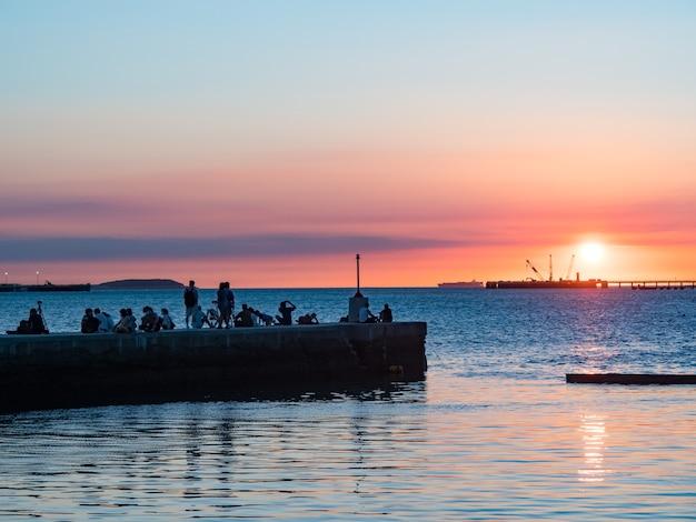 Pôr do sol no porto de pesca de tamsui, taiwan.
