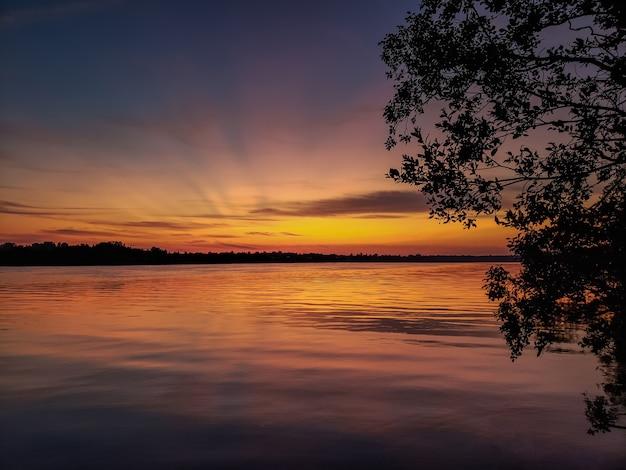 Pôr do sol no rio no verão e cais de madeira