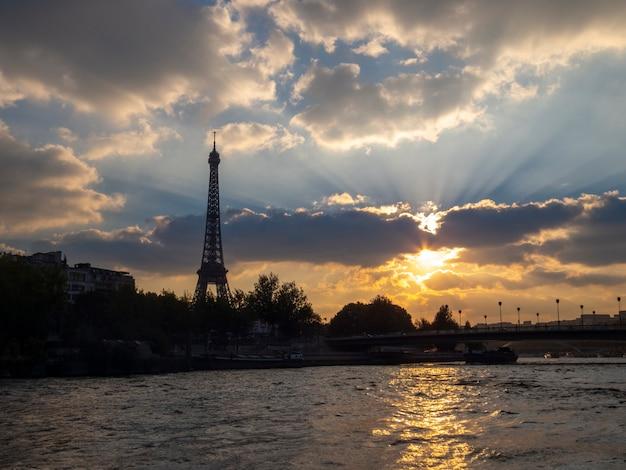Pôr do sol no rio sena em paris, com vista para a torre eiffel.
