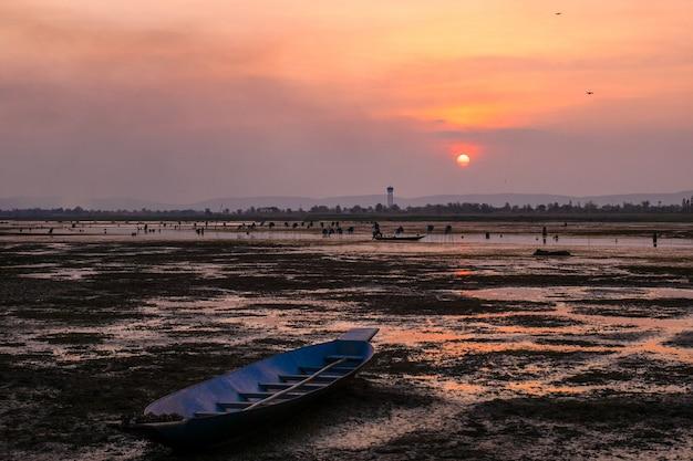 Pôr do sol ou nascer do sol com terra árida e barco de pesca