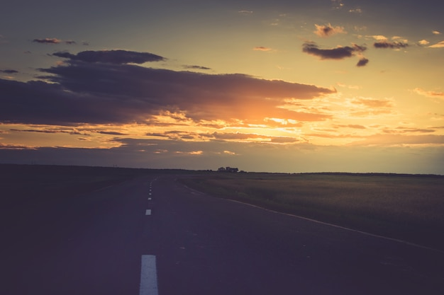 Pôr do sol ou um amanhecer ao longo da estrada que vai para a distância.