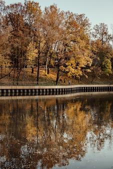 Pôr do sol outonal no lago com árvores refletidas na água