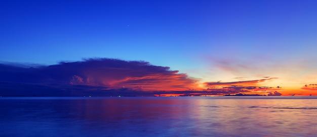 Por do sol panorâmico do céu do mar azul dramático com fundo claro dourado