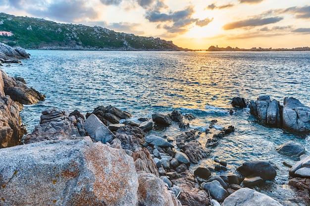 Pôr do sol panorâmico sobre o mar entre as belas rochas de granito de santa teresa gallura, norte da sardenha, itália